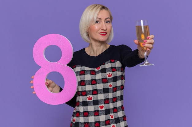 Szczęśliwa młoda kobieta trzyma numer osiem i kieliszek szampana