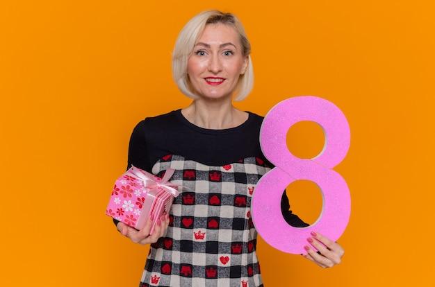 Szczęśliwa młoda kobieta trzyma numer osiem i obecny