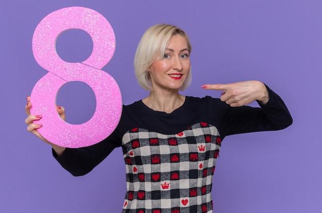 Szczęśliwa młoda kobieta trzyma numer osiem, wskazując palcem wskazującym na to