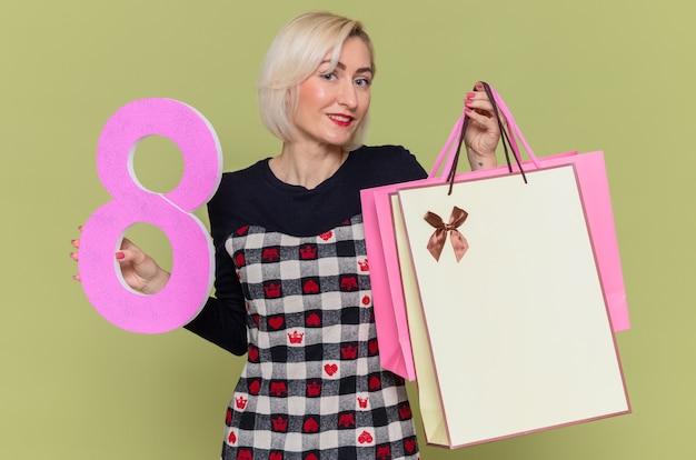 Szczęśliwa młoda kobieta trzyma papierowe torby z prezentami i numer osiem wykonane z tektury