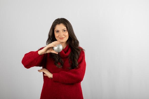 Szczęśliwa młoda kobieta trzyma piłkę boże narodzenie.