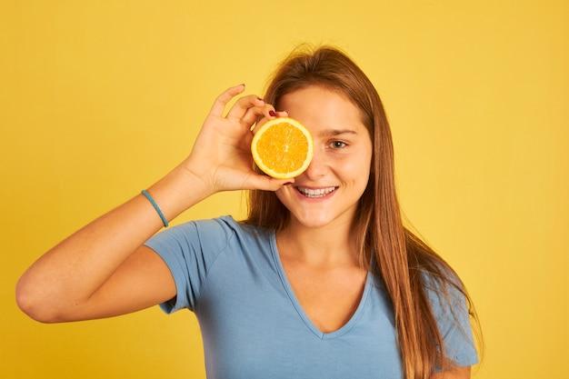 Szczęśliwa młoda kobieta trzyma pomarańczy