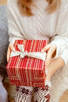 Szczęśliwa młoda kobieta trzyma prezent w otoczeniu pudełek z prezentami siedzi ze skrzyżowanymi nogami na kanapie wielbłąda. prezent na boże narodzenie w rękach dziewczyny, zbliżenie.