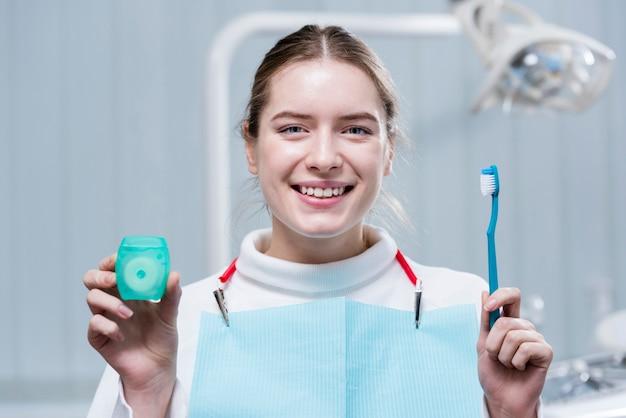 Szczęśliwa młoda kobieta trzyma szczoteczkę do zębów