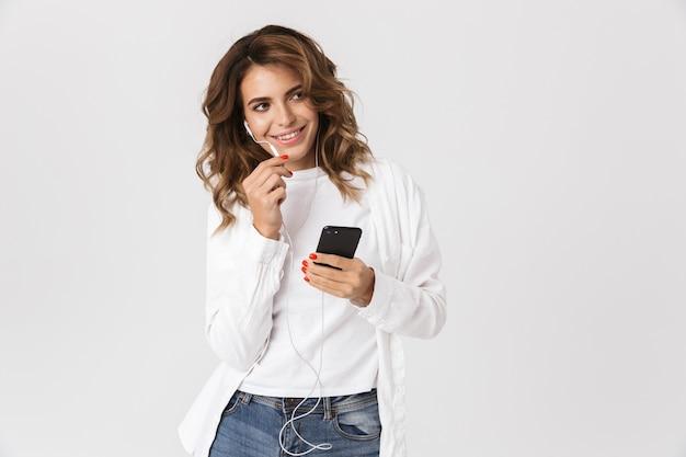 Szczęśliwa młoda kobieta trzyma telefon komórkowy i rozmawia przez głośnik earphpnes na białym tle