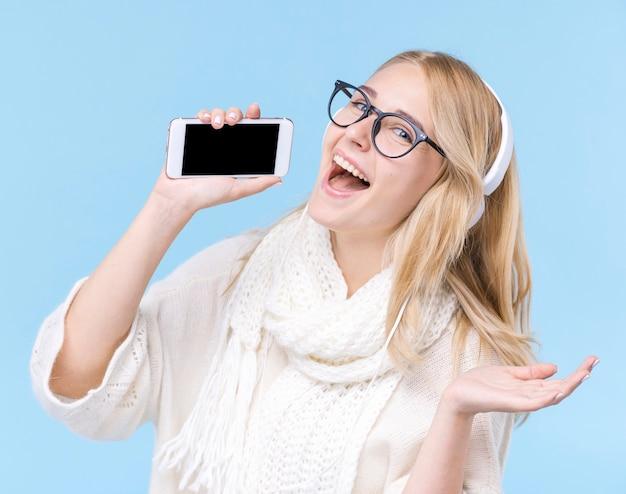 Szczęśliwa młoda kobieta trzyma telefon