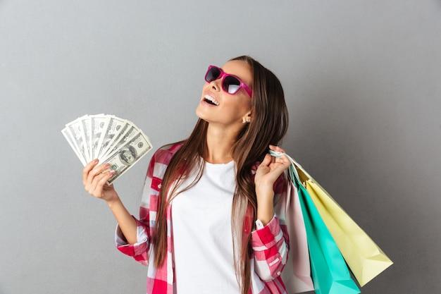 Szczęśliwa młoda kobieta trzyma torba na zakupy i dolarowych banknoty w szkłach