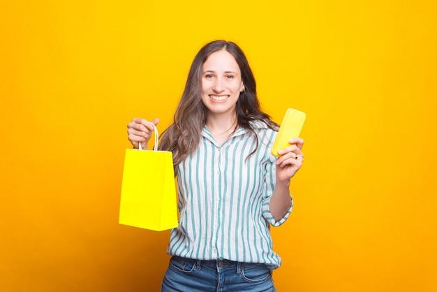 Szczęśliwa młoda kobieta trzyma torbę na zakupy i telefon uśmiecha się do kamery