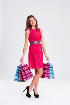 Szczęśliwa młoda kobieta trzyma torby na zakupy