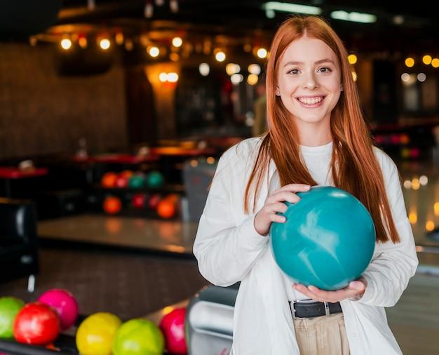 Szczęśliwa młoda kobieta trzyma turkusową kręgle piłkę
