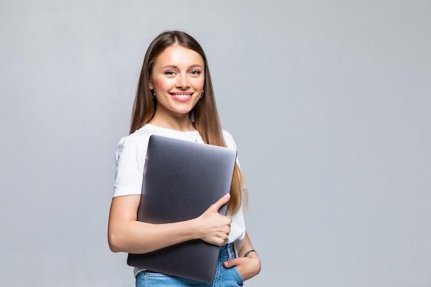Szczęśliwa młoda kobieta trzymając laptop i pozowanie