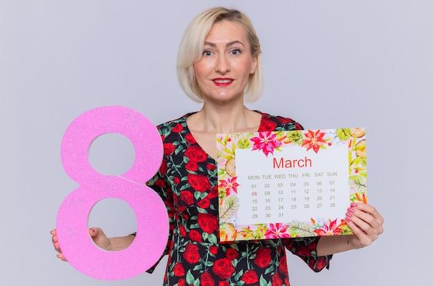 Szczęśliwa młoda kobieta trzymając papierowy kalendarz miesiąca marca i numer osiem uśmiechnięta wesoło z okazji międzynarodowego dnia kobiet marca