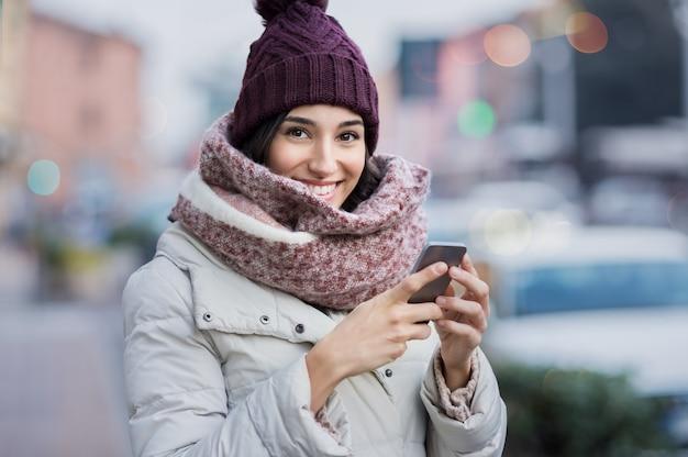 Szczęśliwa młoda kobieta trzymając smartfon i patrząc na kamery