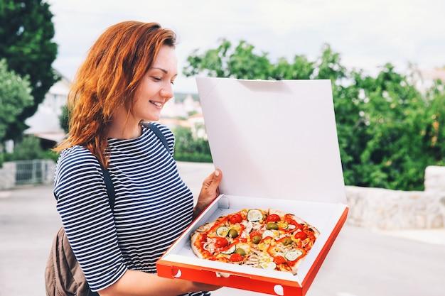 Szczęśliwa młoda kobieta trzymająca gorącą pizzę w pudełku, na zewnątrz na europejskiej ulicy