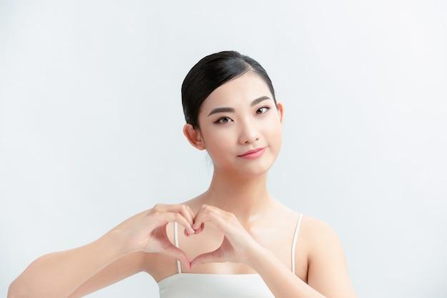 Szczęśliwa młoda kobieta trzymająca ręce w kształcie serca w pobliżu klatki piersiowej