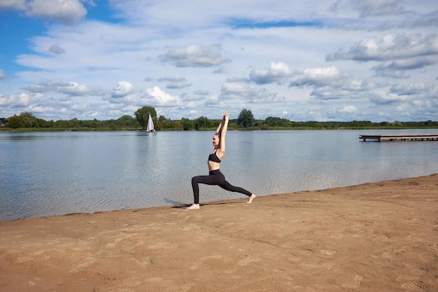 Szczęśliwa młoda kobieta ubrana w czarną odzież sportową uprawiania jogi na piasku w pobliżu jeziora na świeżym powietrzu.