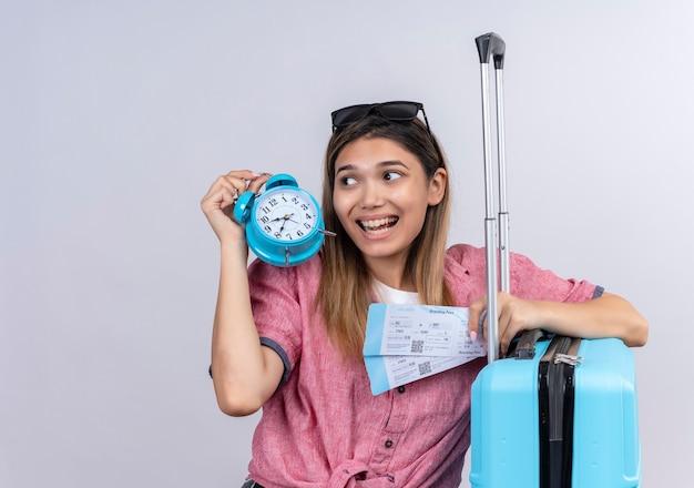 Szczęśliwa młoda kobieta ubrana w czerwoną koszulę i okulary przeciwsłoneczne patrząc z boku, trzymając budzik z biletami lotniczymi i niebieską walizką na białej ścianie