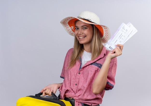 Szczęśliwa młoda kobieta ubrana w czerwoną koszulę, trzymając żółtą walizkę i pokazując bilety lotnicze, patrząc na białej ścianie