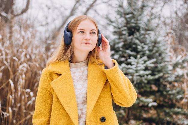 Szczęśliwa młoda kobieta ubrana w płaszcz lsłuchanie muzyki w słuchawkach