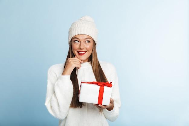 Szczęśliwa młoda kobieta ubrana w sweter gospodarstwa obecne pudełko