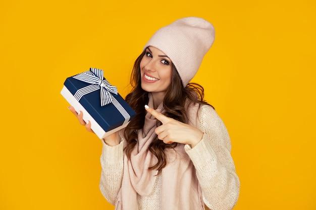 Szczęśliwa młoda kobieta uśmiecha się palcem wskazującym, trzymając w ręku niebieskie pudełko. prezent dla twojego ukochanego mężczyzny. dziewczyna w swetrze patrzy i wskazuje na prezent.