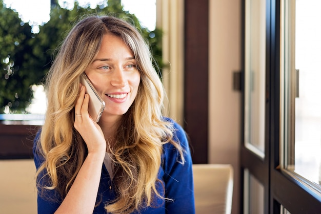 Szczęśliwa młoda kobieta uśmiecha się podczas rozmowy przez telefon