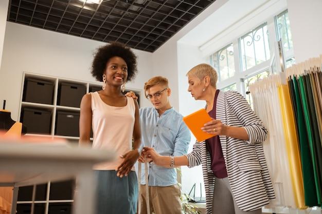 Szczęśliwa młoda kobieta uśmiecha się stojąc obok swoich kolegów w studio, wykonując pomiary