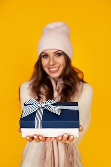 Szczęśliwa młoda kobieta uśmiecha się, trzyma i wyciąga z przodu daje niebieskie pudełko jej ukochanemu mężczyźnie prezent gwiazdkowy. dziewczyna w swetrze wygląda i daje prezent.