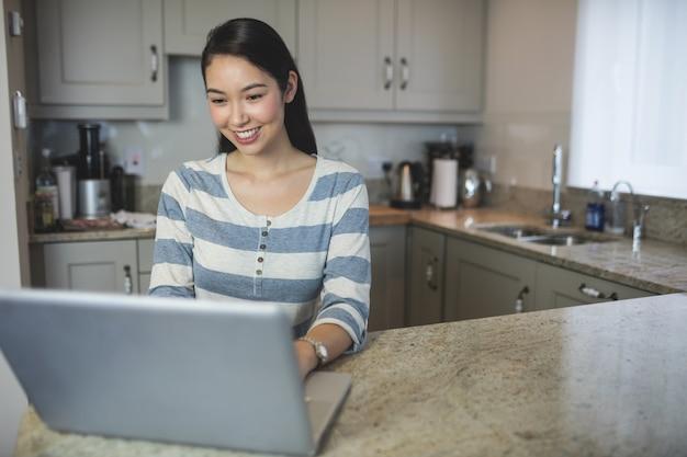 Szczęśliwa młoda kobieta używa laptop w kuchni