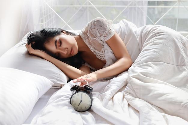 Szczęśliwa młoda kobieta w białej bieliźnie leżąc w łóżku, obudź się późno i zaspał rano, próbując zatrzymać budzik. śliczna dziewczyna wygląda wygodnie, potrzebuje więcej snu. trudny poranek wstać koncepcja