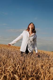 Szczęśliwa młoda kobieta w białej koszuli w polu pszenicy. słoneczny dzień. dziewczyna uśmiechnięta, koncepcja szczęścia. ręce na bok. zdjęcie pionowe