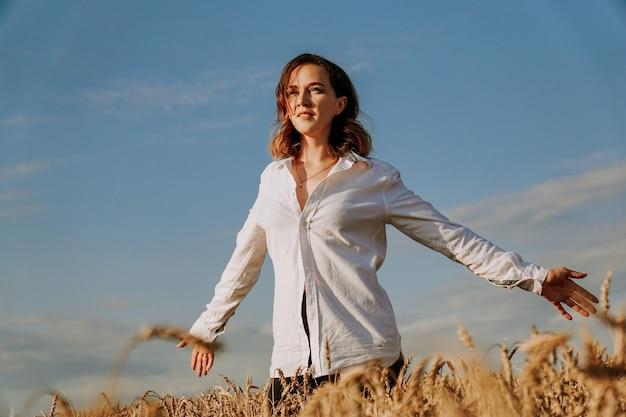 Szczęśliwa młoda kobieta w białej koszuli w polu pszenicy. słoneczny dzień. dziewczyna uśmiechnięta, koncepcja szczęścia. ręce z boku
