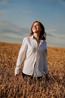Szczęśliwa młoda kobieta w białej koszuli w polu pszenicy. słoneczny dzień. dziewczyna uśmiechnięta, koncepcja szczęścia. zdjęcie pionowe
