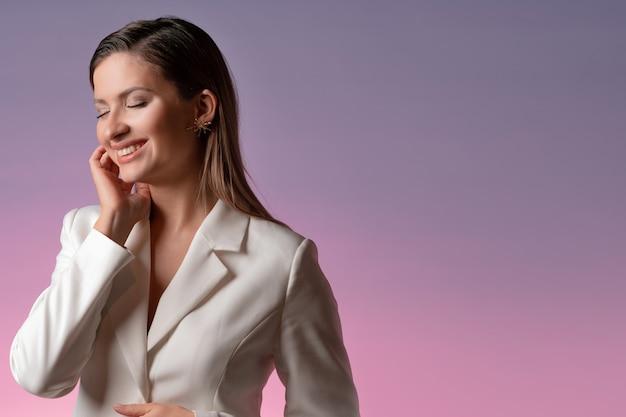 Szczęśliwa młoda kobieta w białej kurtce uśmiecha się