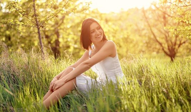 Szczęśliwa młoda kobieta w białej sukni uśmiechnięta i odwracająca wzrok, siedząc na świeżej zielonej trawie w słoneczny letni dzień na wsi i odpoczywając
