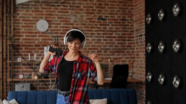 Szczęśliwa młoda kobieta w białych słuchawkach cieszyć się słuchaniem ulubionej muzyki na smartfonie.