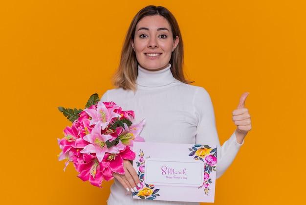 Szczęśliwa młoda kobieta w białym golfie trzyma kartkę z życzeniami i bukiet kwiatów