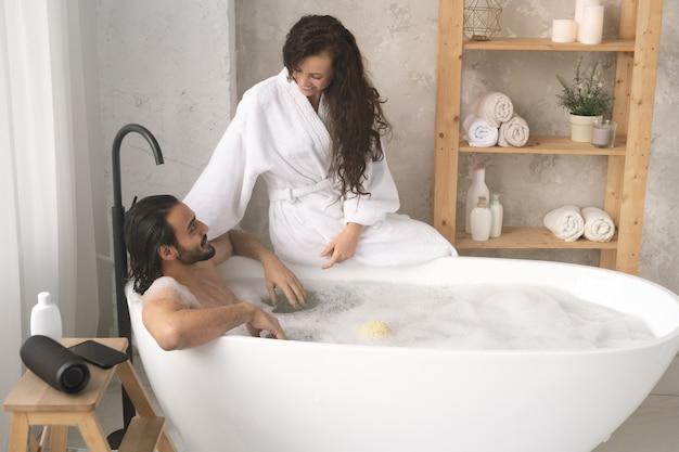 Szczęśliwa młoda kobieta w białym szlafroku siedzi na wannie i mówi do męża, ciesząc się kąpiel z pianką