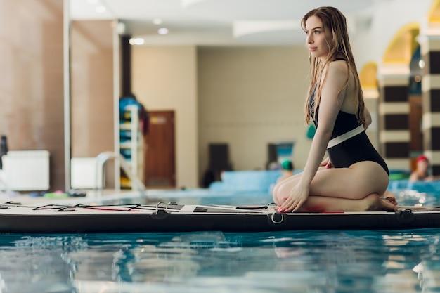 Szczęśliwa młoda kobieta w bikini opala się na desce surfingowej w basenie instruktora na krytym ...