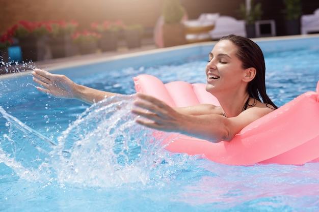 Szczęśliwa młoda kobieta w bikini z nadmuchiwanym gumowym materacem, bawiąc się i dobrze się bawiąc w basenie z wodą w gorący letni dzień, będąc mokrą