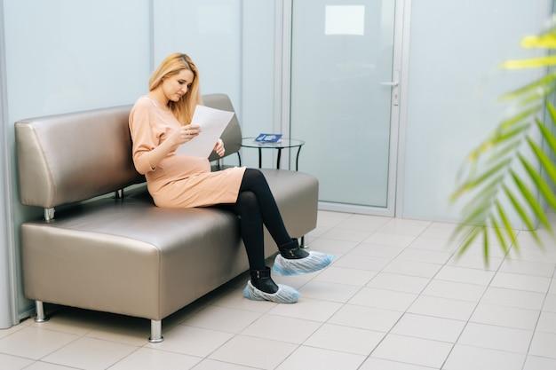 Szczęśliwa młoda kobieta w ciąży siedzi w korytarzu szpitala, czekając na wizytę ginekologa