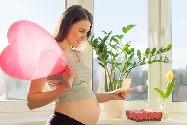 Szczęśliwa młoda kobieta w ciąży z pudełkiem i balonem serca