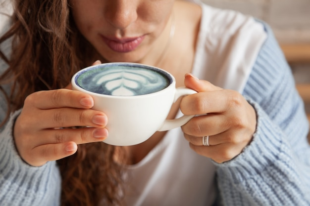 Szczęśliwa młoda kobieta w ciepły sweter z dzianiny, trzymając rękami kubek zdrowej gorącej niebieskiej kawy latte. niebieska kawa latte ze świeżymi ziarnami kawy i herbatą z groszku motylkowego bluechai. koncepcja dobrego samopoczucia.