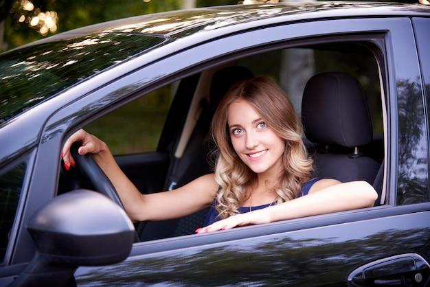 Szczęśliwa młoda kobieta w czarnym samochodzie.