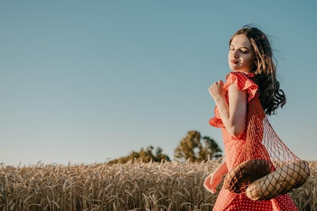 Szczęśliwa młoda kobieta w czerwonej sukience z chleba i próżnuje w torbie sklep spożywczy netto