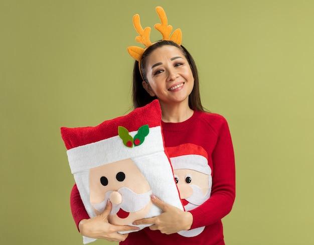 Szczęśliwa młoda kobieta w czerwonym swetrze boże narodzenie na sobie zabawną obręcz z rogami jelenia, trzymając świąteczną poduszkę patrząc uśmiechnięty radośnie