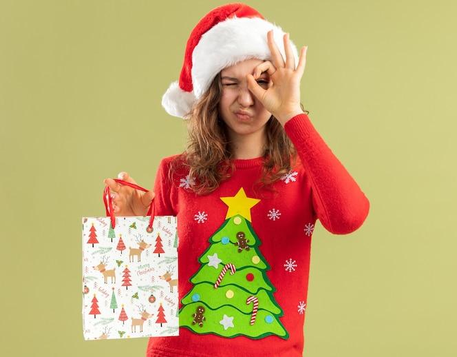 Szczęśliwa młoda kobieta w czerwonym świątecznym swetrze i santa hat trzymając papierową torbę z prezentem świątecznym mrugając patrząc przez ok znak stojący nad zieloną ścianą
