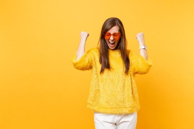 Szczęśliwa młoda kobieta w futrzanym swetrze, serce pomarańczowe okulary krzyczy i zaciska pięści jak zwycięzca na białym tle na jasnożółtym tle. ludzie szczere emocje, koncepcja stylu życia. powierzchnia reklamowa.
