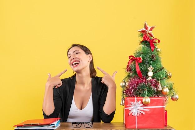 Szczęśliwa młoda kobieta w garniturze z dekorowaną choinką w biurze