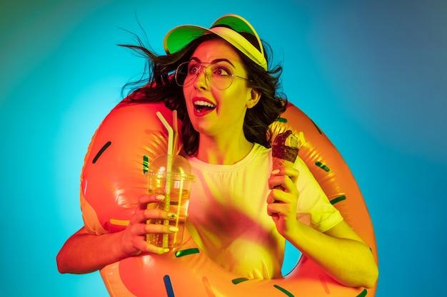 Szczęśliwa młoda kobieta w gumowym pierścieniu z lodami i napojem na modnym niebieskim neonie